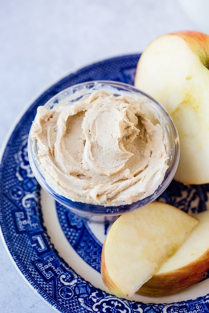 a blue dish holding a sliced apple and half of an apple with a small dish of healthy peanut butter greek yogurt dip