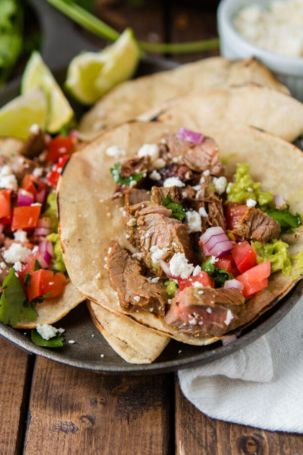Two delicious authentic carne asada tacos with mexican cheese, onions, steak, cilantro and guacamole on a serving plate on top of a wooden table.