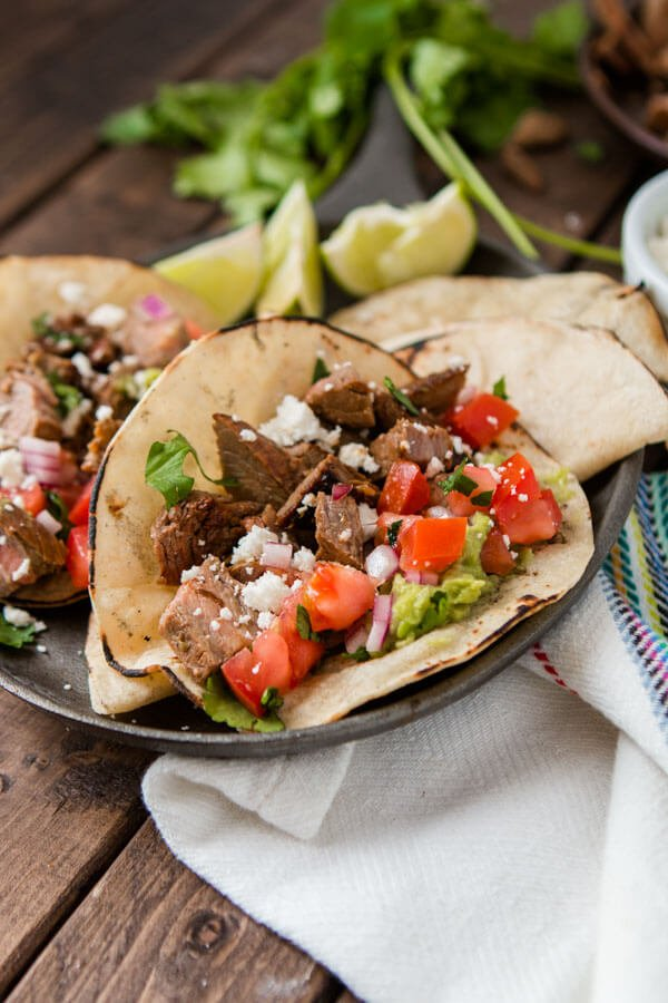 Two easy and delicious authentic carne asada tacos on a small serving plate with a white cloth on a wooden table.