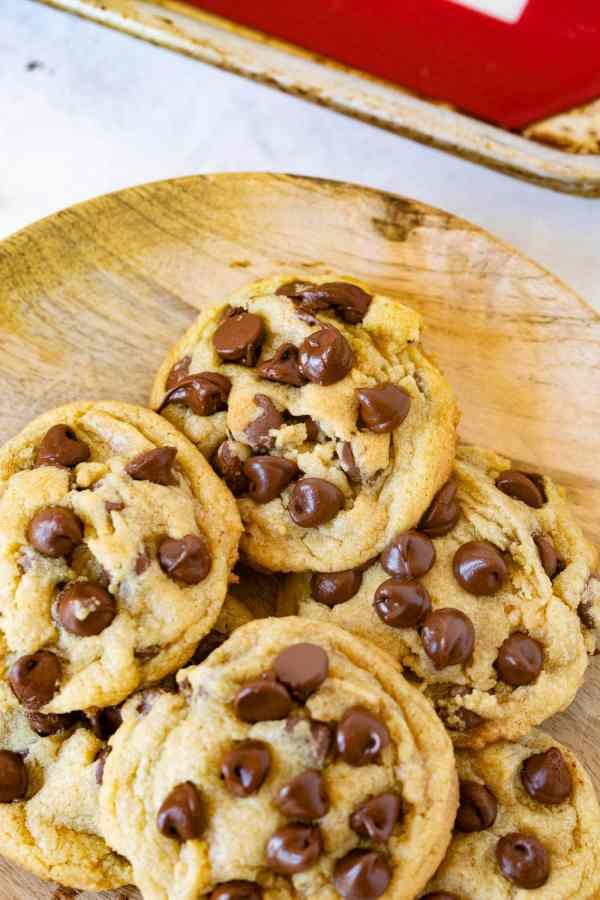 A photo of a wooden plate full of chocolate chip pudding cookies.