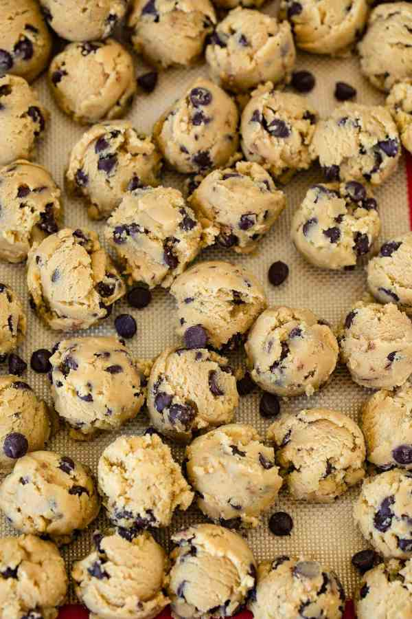 A photo of a sheet pan full of balls of homemade chocolate chip cookie dough.