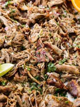 Pork carnitas crispy and shredded sitting on a sheet pan with lime wedges and topped with chopped fresh cilantro.