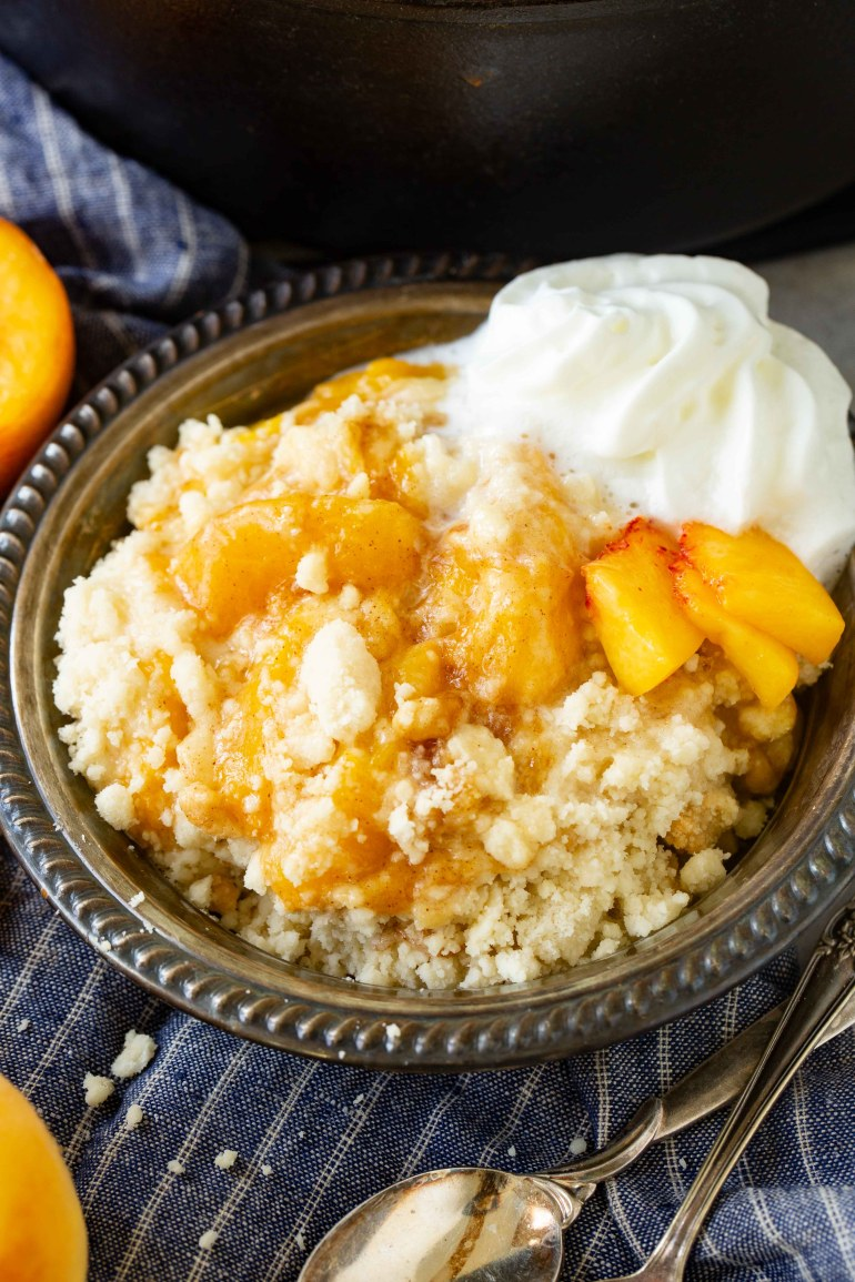 a metal bowl with fresh, juicy peach cobbler and a dollop of whipped cream all on a blue napkin