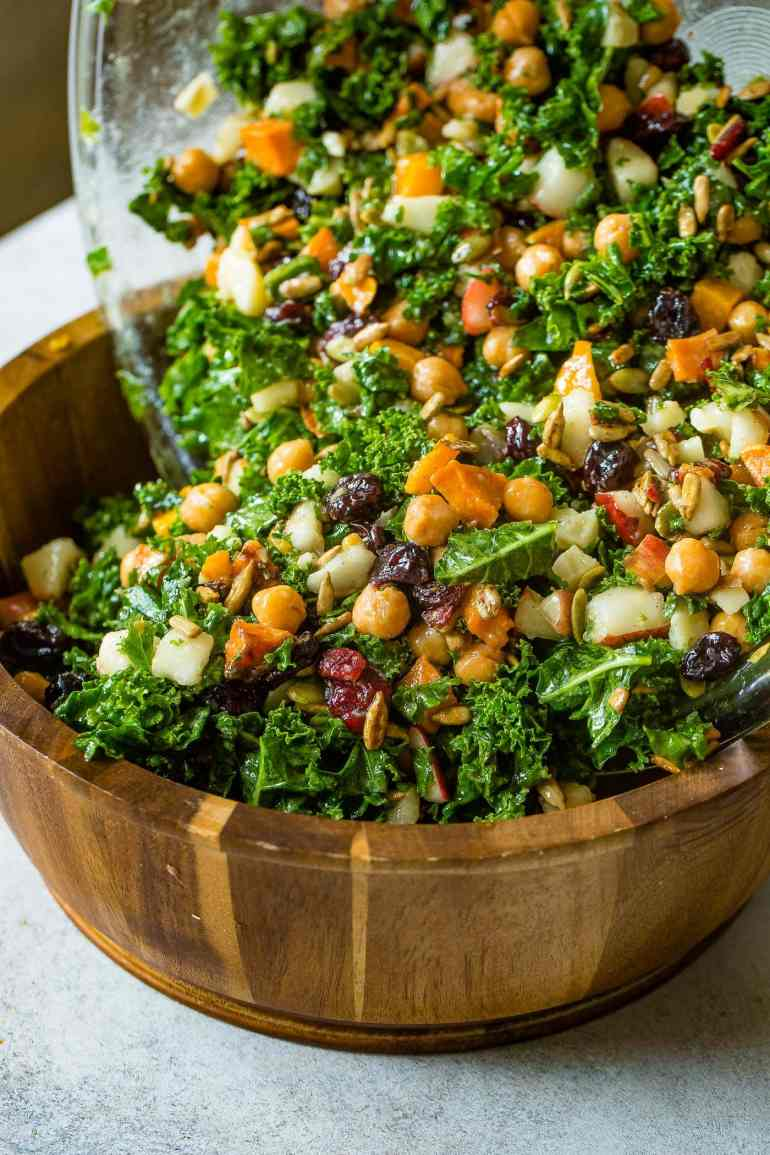 A photo of a large wooden bowl full of kale salad topped with roasted butternut squash, craisins, chickpeas, pepitas, and gouda cheese all being tossed.