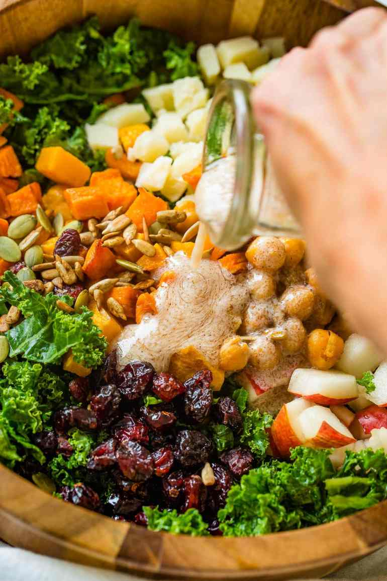 A photo of dressing being poured on a large wooden bowl full of kale salad topped with roasted butternut squash, craisins, chickpeas, pepitas, and gouda cheese.