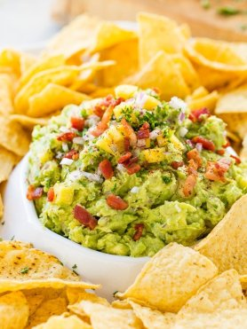 a large chips and dip platter with corn tortilla chips and mango bacon guacamole piled high in the center
