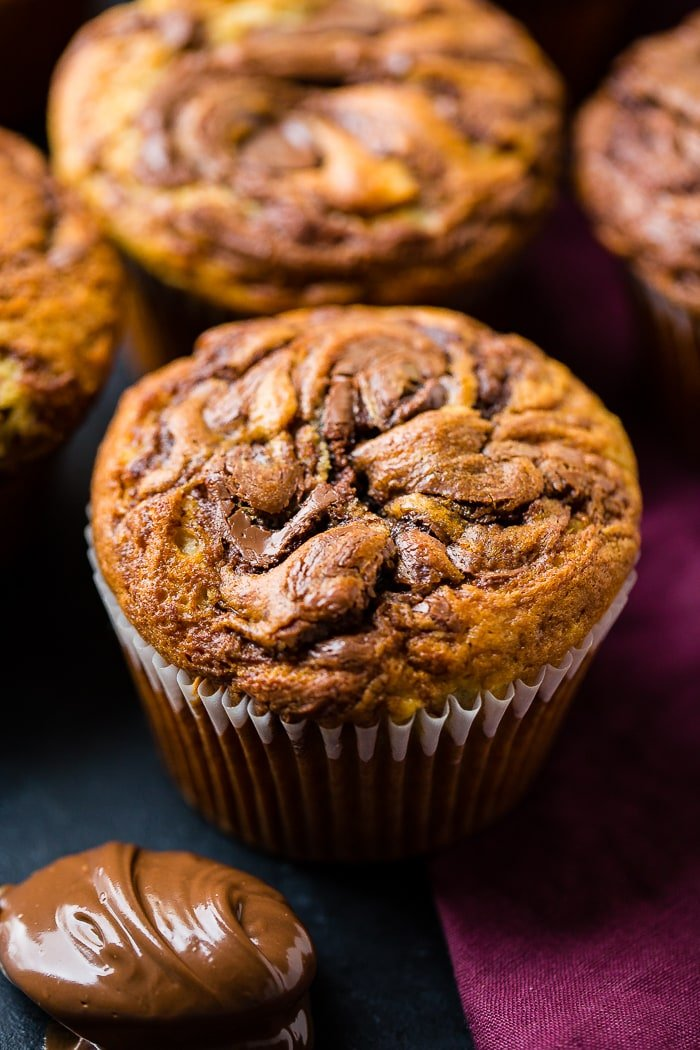 A nutella swirled banana muffin surrounding by more muffins