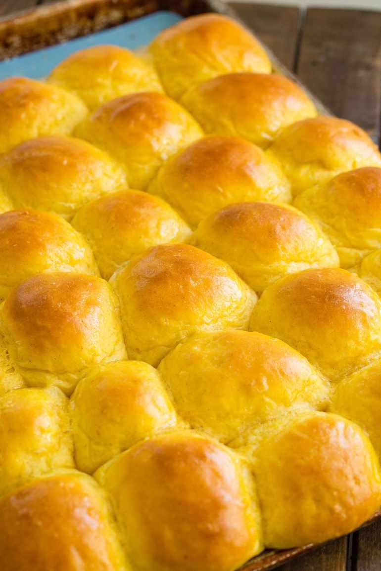 a cookie sheet full of soft pumpkin dinner rolls with buttered tops
