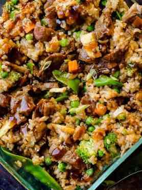 a glass casserole dish with fried rice, carrots, peas, broccoli, snow peas, and teriyaki beef
