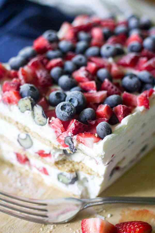 Looking for the ultimate 4th of July dessert? This Red White and Blue Icebox Cake is a simple and festive recipe for a crowd! No baking required and only a few ingredients to layer and put this icebox cake together! whip cream, blueberries, strawberries, graham crackers