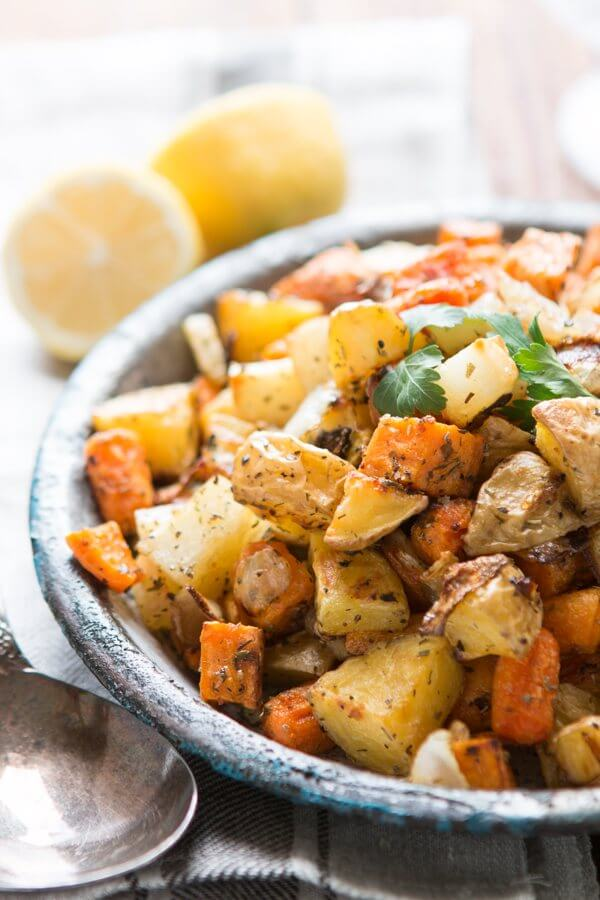 roasted root vegetables in serving bowl next to spoon