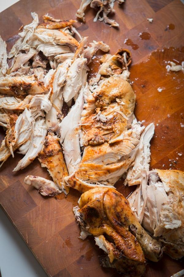 Shredded Slow Cooker Whole Chicken on a wood cutting board.