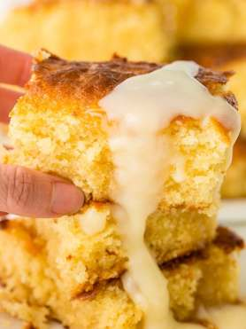 A photo someone holding a piece of homemade sweet cornbread with honey butter dripping off it.