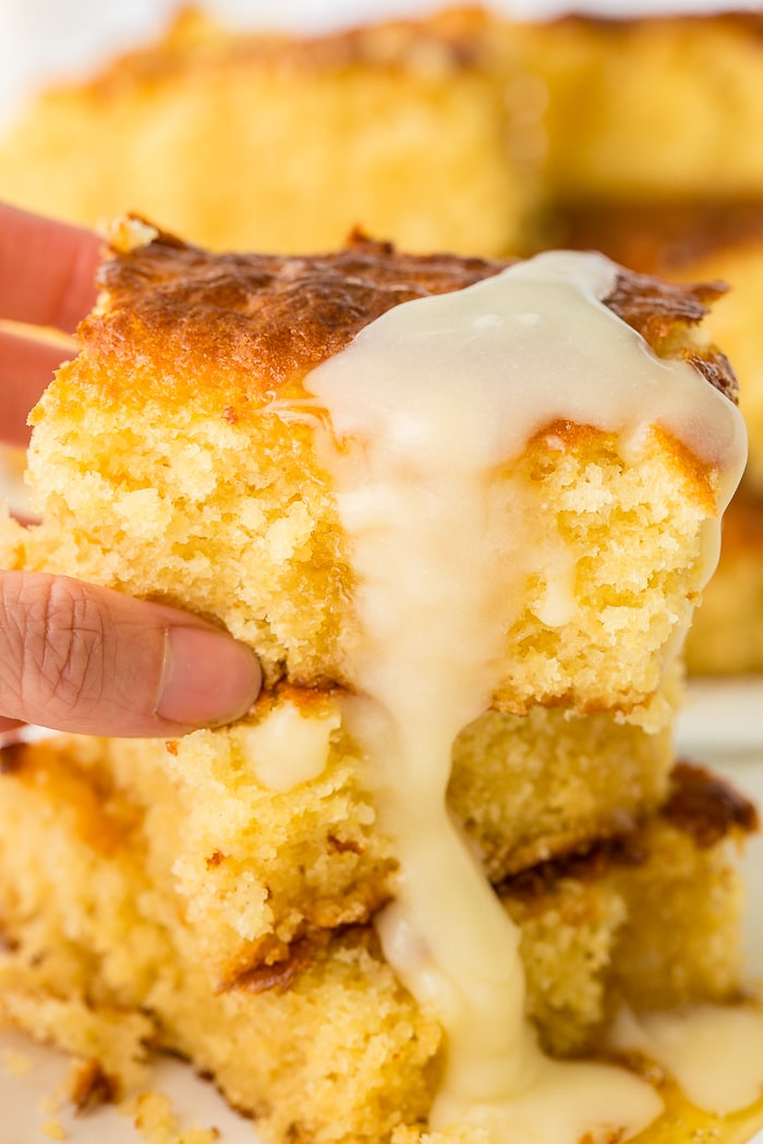 three moist cornbreads stacked with a drizzle of honey butter dripping down