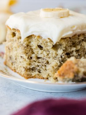a slice of moist banana cake with cream cheese frosting and a bit taken out of it all