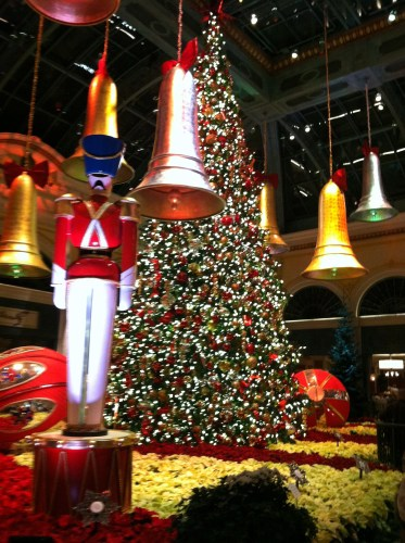A soldier stands at attention near the centerpiece Christmas tree at Bellagio