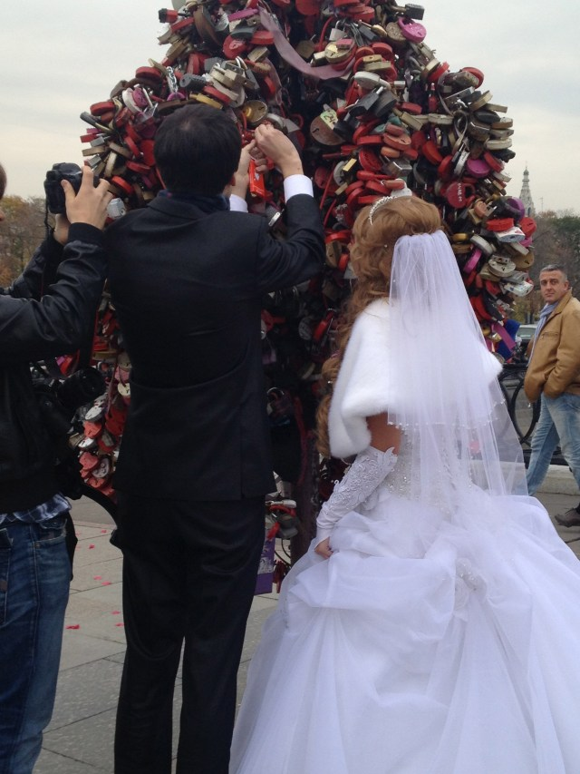 Bride and groom in Moscow celebrating Russian tradition of adding a love padlock to a wedding tree to symbolize their love.