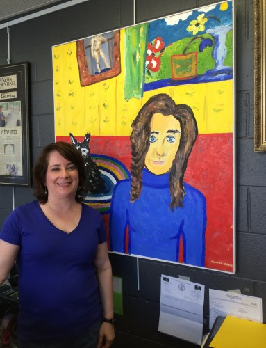 Shannon Davis poses in front of her colorful self-portrait.