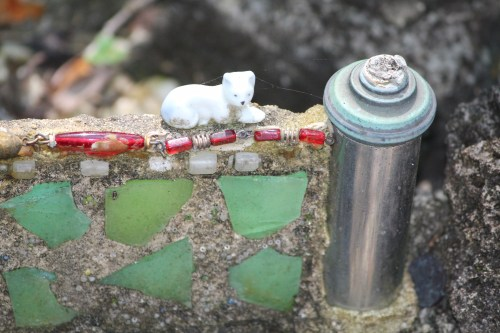 Tiny cat, glass shards, metal cylinder form a wall at Ave Maria Grotto