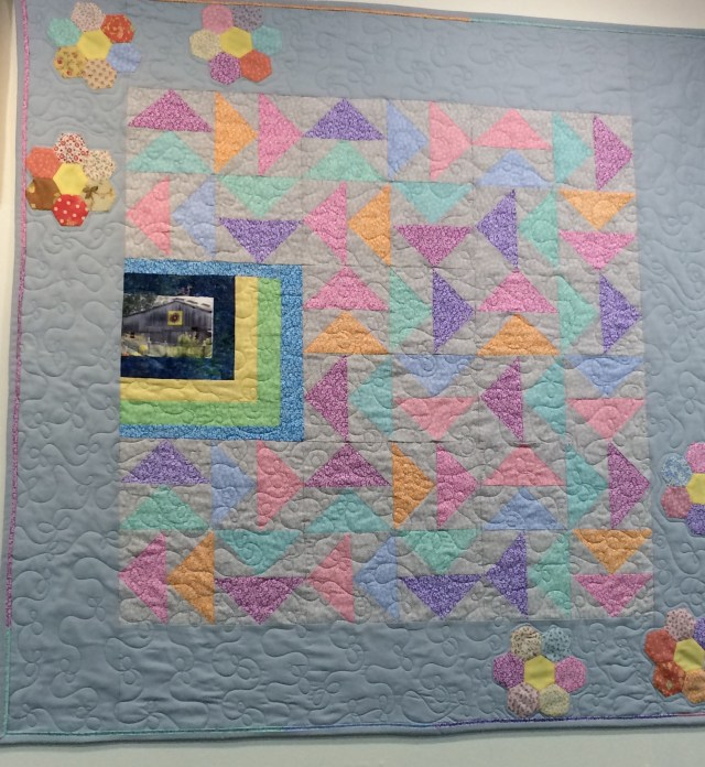 On the wall of Mountain Stitches by Susan in Gatlinburg, TN is this off-center log cabin square set into a quilt of an original design.