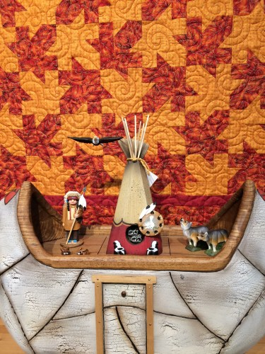 A colorful quilt forms the backdrop for a folk art boat at Tamarack.