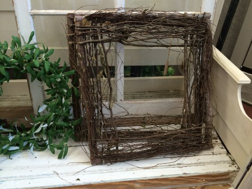 Square grapevine wreath on a painted bench.