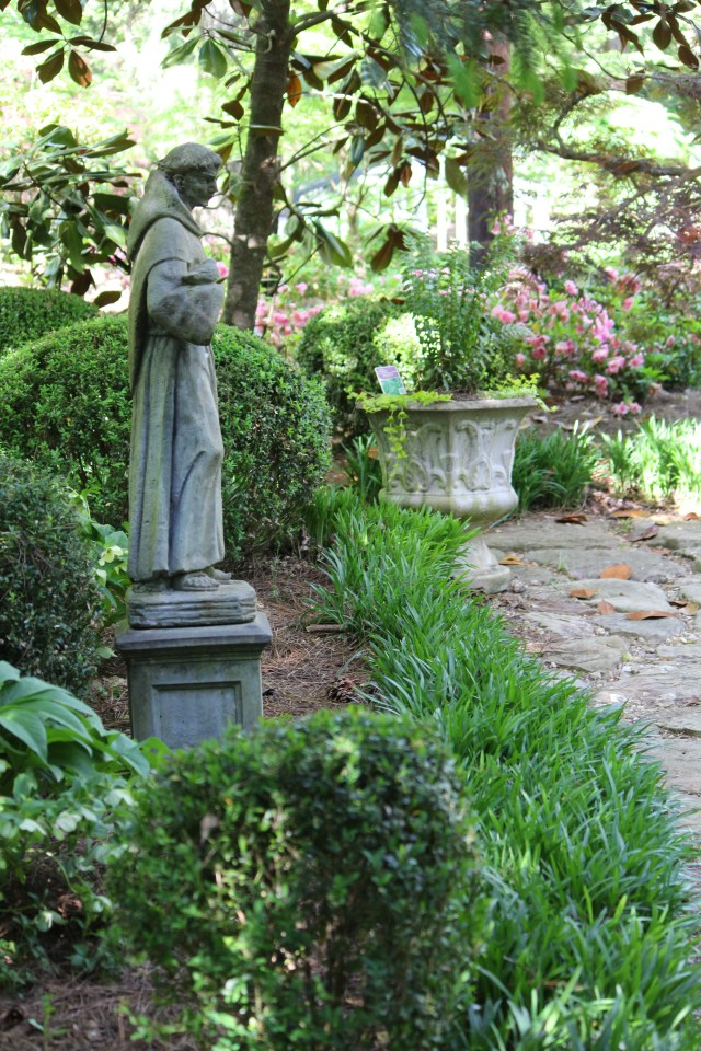 Statuary and concrete planters define areas of Dr. Milan's garden.
