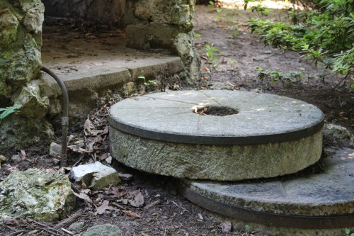 Curved edges of millstones stacked as stepping stones in Savage Gardens.