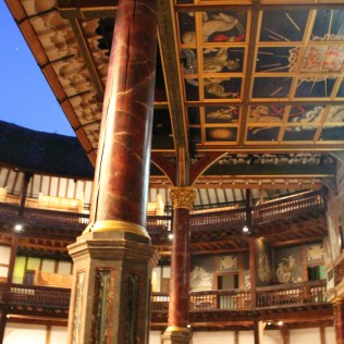 Faux-painted columns flank the stage with a hand-painted ceiling,