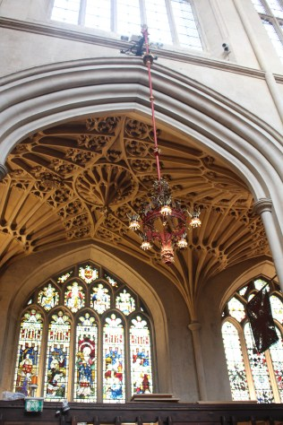 Intricate stained glass windows framed by fan vaulting