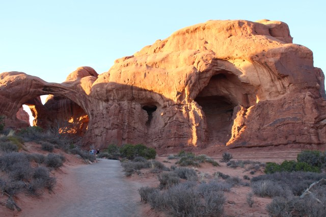 Rays of the sun light up the structure known as Double Arch in Arches National Park.