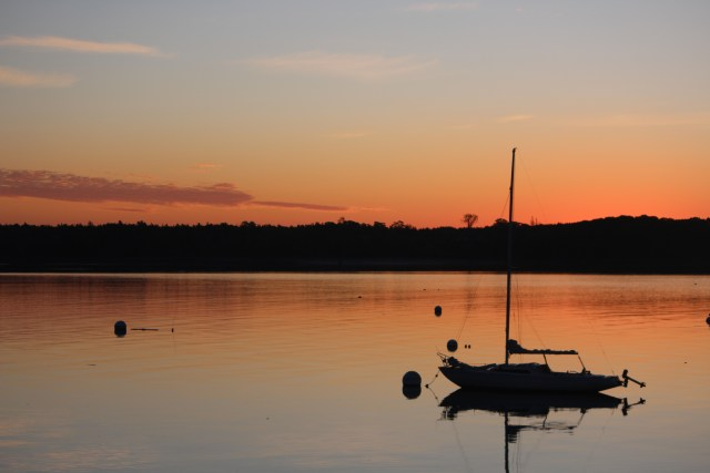 A boat is silhouetted by the orange-turned-pink sunrise in Castine, Maine.