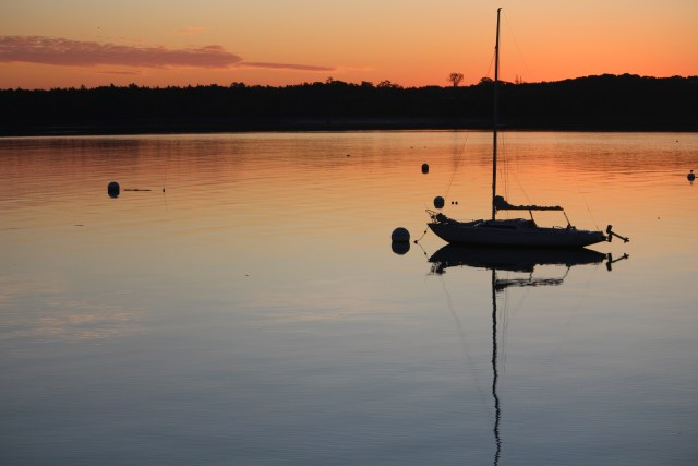 Aglow in morning light, a lone tethered boat stands ready.