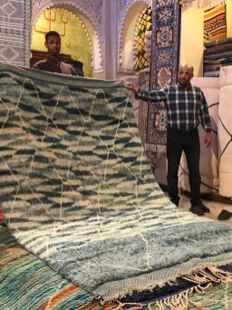 Rug salesmen unfold rugs while we watch in the Marrakech medina.