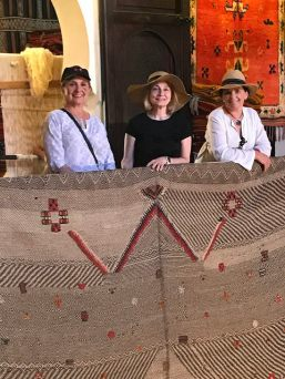 Three ladies find a handsome Berber rug in the Marrakech medina.