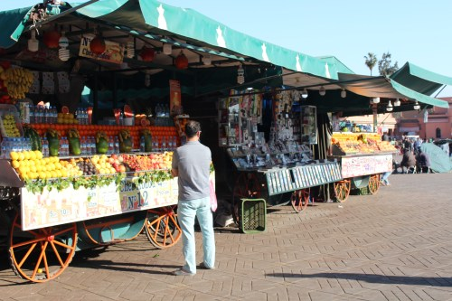 Stalls open up offering fruit and tourist trinkets on the plaza known as Jemaa el-Fnaa.