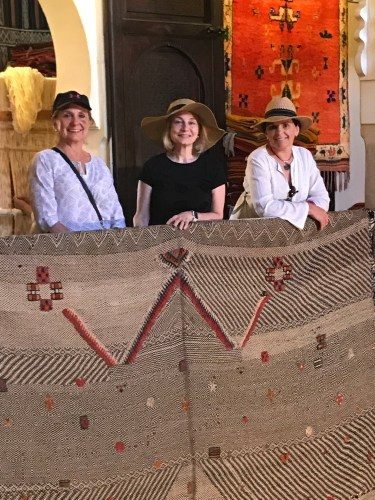Admiring this dramatic but simple rug with woven symbols are three shoppers from California.