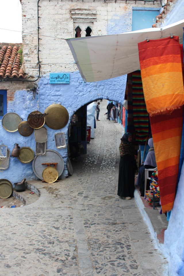A walk through Chefchaouen takes you past shopkeeper's wares, through blue-painted arches, and over uneven cobblestone streets.