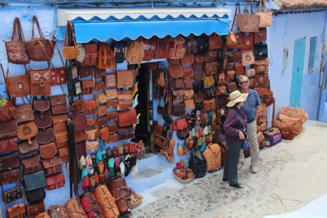 Leather goods, perhaps made at the tannery in Fez, frame a doorway in Chefchaouen.