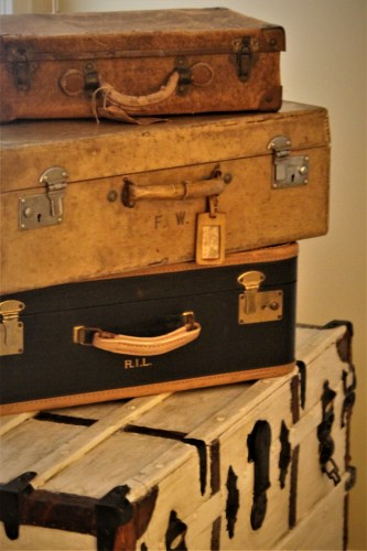 Stack of suitcases on an old steamer trunk
