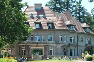 The stately Pittock Mansion and its picture window looking out to the city of Portland.