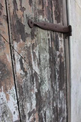 Hand-forged door hinge on weathered door, French Quarter