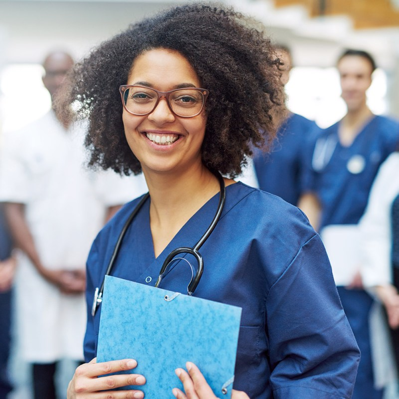 nurse wearing blue scrubs and smiling alongside a team of doctors and nurses