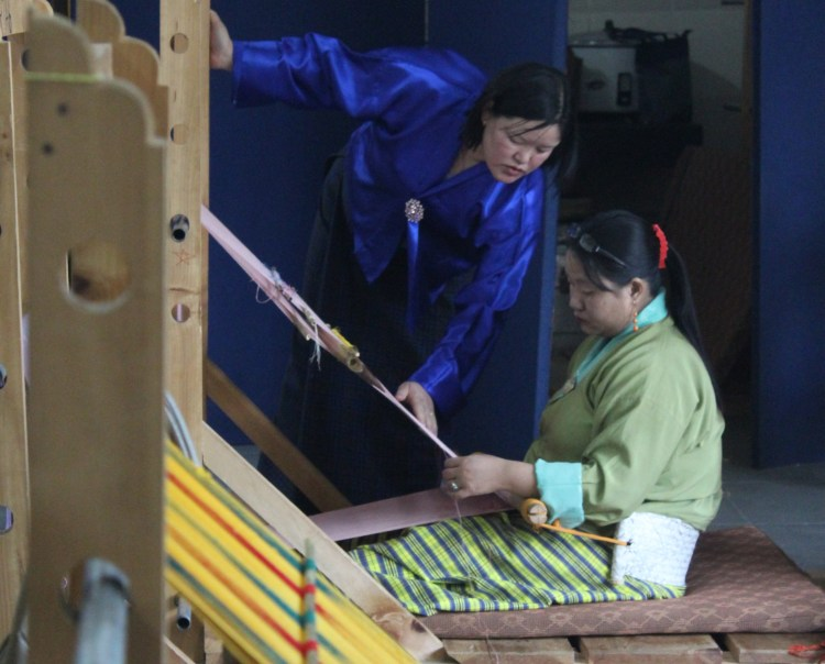 A Bhutanese weaver has her work examined in Thimphu.