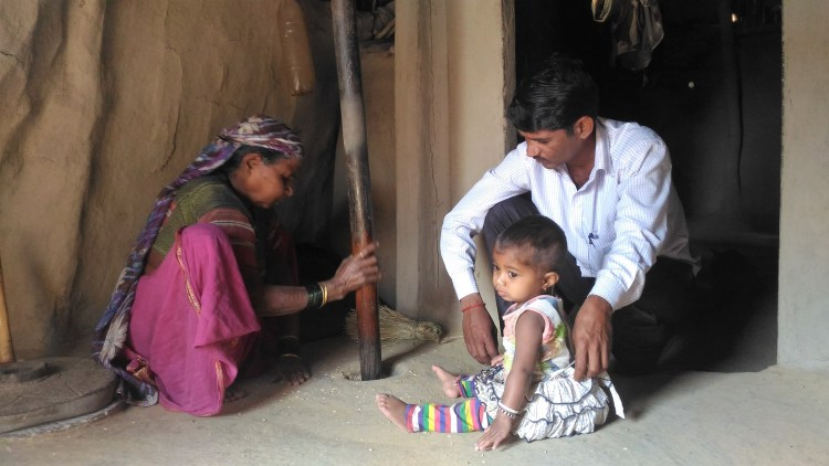 My guide, Balu's mother pounds rice to loosen the husk from the kernels as her granddaughter looks on.