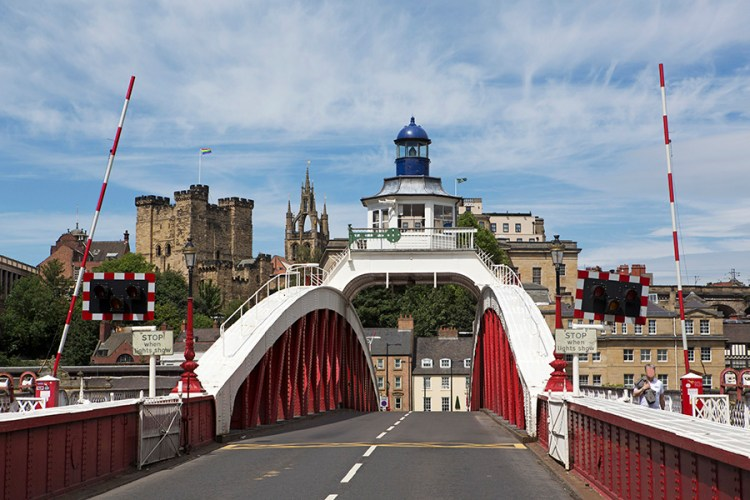 The Swing Bridge, spanning the River Tyne between Gateshead and Newcastle-upon-Tyne in England. The Norman castle keep and Quayside area of Newcastle stand beyond the bridge.