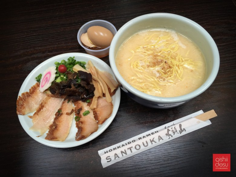 Photo Description: the Santouka Ramen spread of their signature thick sided bowl, a plate separate plate with chashu, kikurage, menma, negi, naruto, and umeboshi. The third topping is the egg.