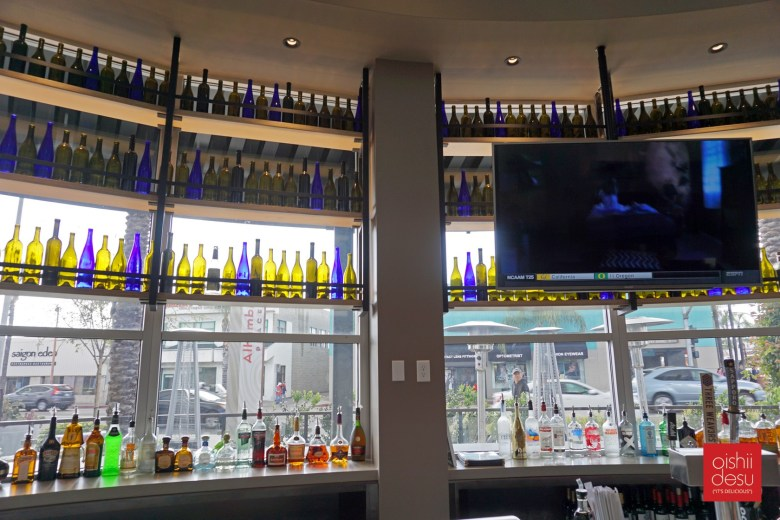 Photo Description: the bar are at Tokyo Table. The large glass windows surround the bar, along with a number of yellow and blue bottles.