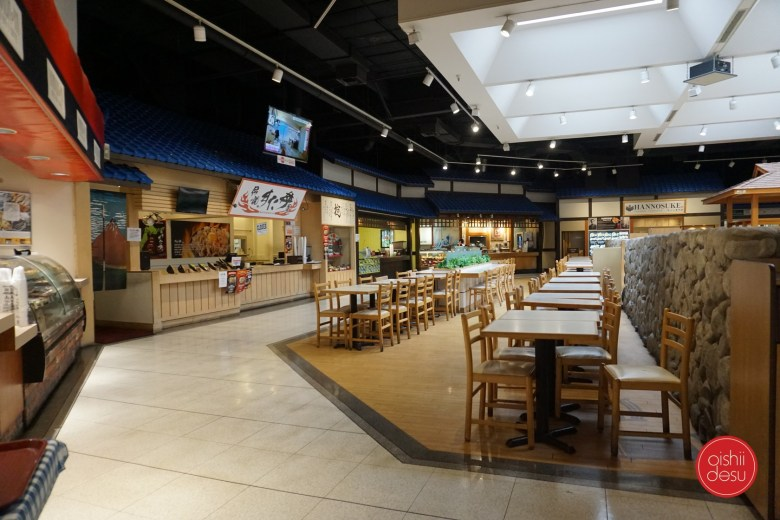 Photo Description: Mitsuwa market food court is a large octagon shape with several individuals restaurants in each segment of the wall. Each restaurant has it's own unique style although they are all very traditionally Japanese looking. In the center is the seating area, along with a large faux stone brick wall.