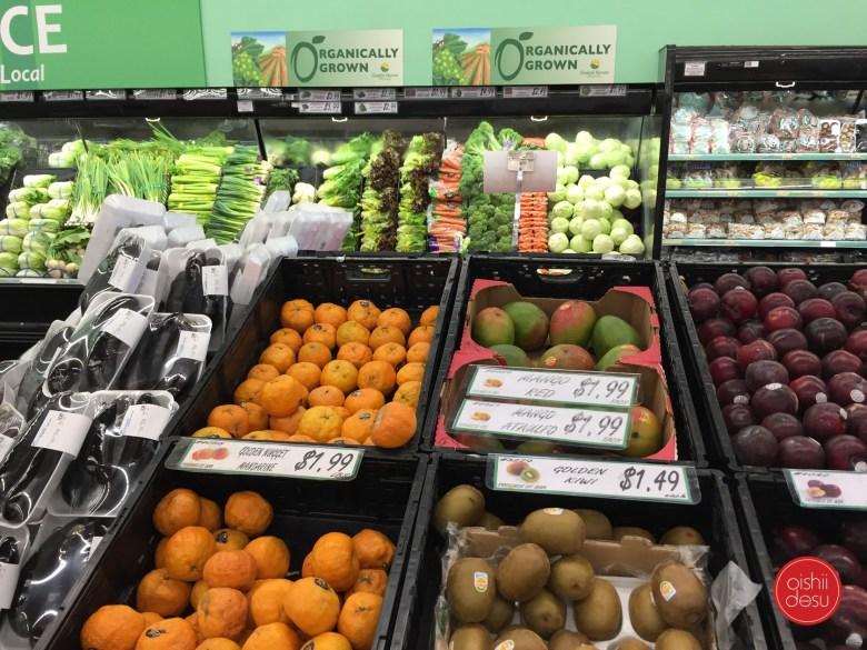 Photo Description: large bins of vegetables to fruit can be seen. The same produce you would find in any mainstream market from a variety of mushrooms, green onions, carrots, cabbage to tangerines, mango, kiwi, and apples.